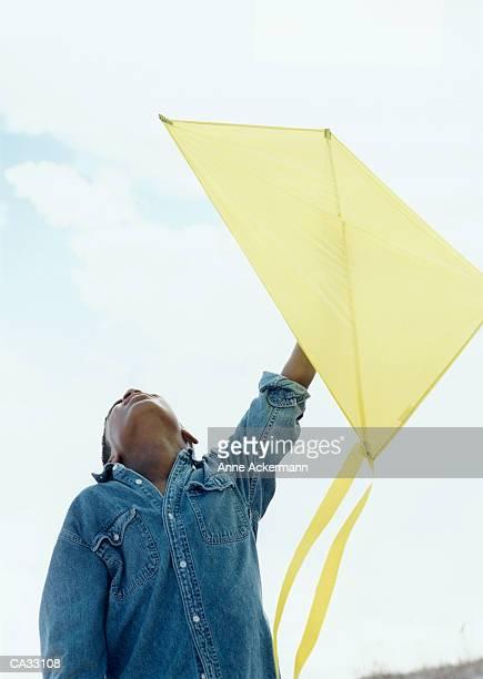 Boy (10-12) holding yellow kite