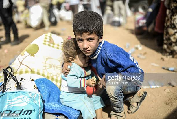 A boy holds a baby as Syrian Kurds fleeing an onslaught by the jihadist Islamic State group cross the border between Syria and Turkey at the...