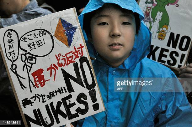 A boy holds a banner denouncing nuclear power plants during a protest in front of the official residence of Japanese Prime Minister Yoshihiko Noda in...