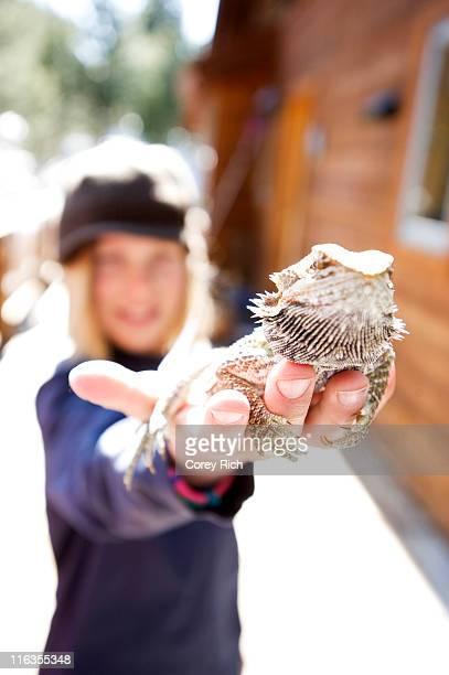 A boy holds a bearded dragon while playing outdoors in Lake Tahoe, California.