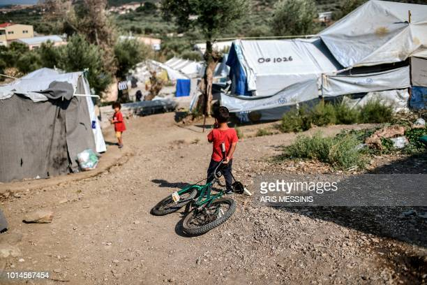 A boy holds a bicycle at a camp next to the Moria refugee camp in the island of Lesbos on August 5 2018