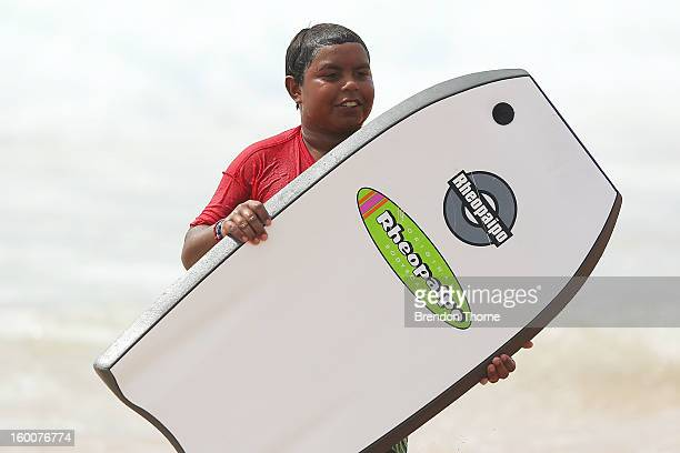 A boy holds a bodyboard as Indigenous children from Brewarrina experience their first trip to the ocean on January 26 2013 in Sydney Australia The...