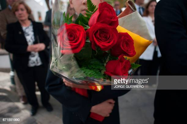 A boy holds a bouquet of red roses during funerals for former Franco minister Jose Utrera Molina in Nerja on April 22 2017 One of the last ministers...
