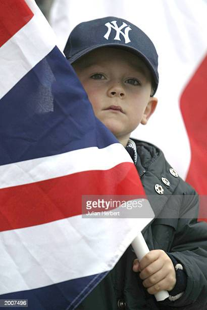 A boy holds a British flag as the aircraft carrier HMS Ark Royal returns to her base 126 days after she set sail May 17 2003 in Portsmouth England...