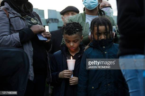 A boy holds a candle as family friends and community members attend a vigil at the intersection where Manuel Ellis a 33yearold black man died in...