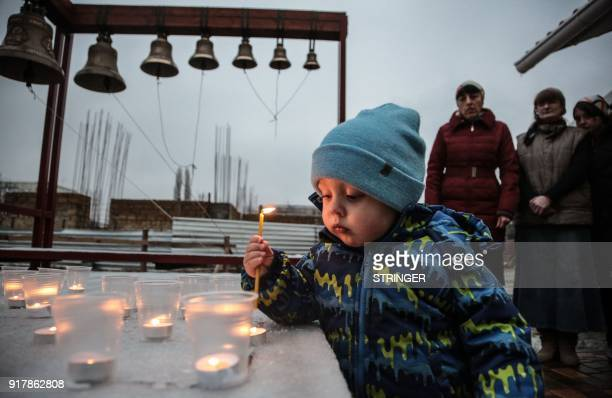 TOPSHOT A boy holds a candle during a church service in Simferopol on February 13 in commemoration of the victims of the plane crash The Antonov...