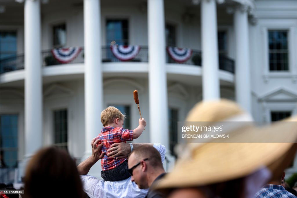 A boy holds a corn dog as people wait to hear US President Donald Trump speak during an Independence Day picnic for military families on the South Lawn of the White House, July 4, 2018 in Washington, DC.