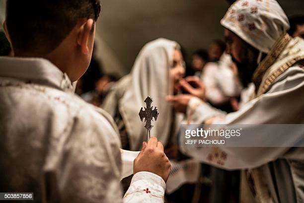 A boy holds a cross as Coptic priest father Bedaba gives communion during Christmas mass on January 6 2016 in a Coptic Orthodox monastery in...