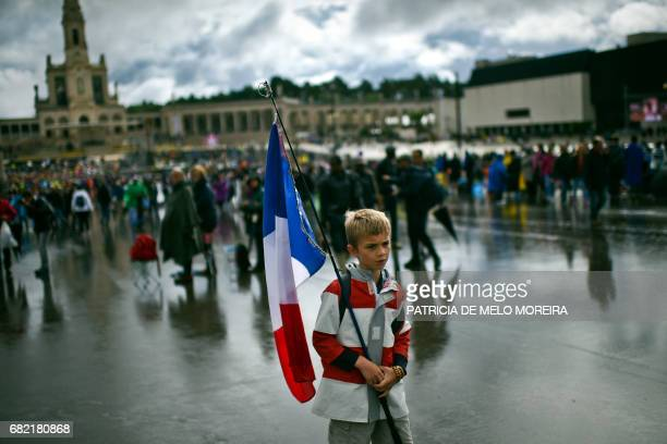 A boy holds a French flag at Fatima Sanctuary in Fatima central Portugal on May 12 2017 Two of the three child shepherds who reported apparitions of...