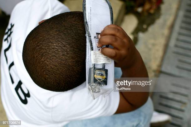 A boy holds a gun lock above his head at an anti gun violence rally on the Art Museum steps in Philadelphia PA on June 11 2018 The 3rd annual Fill...