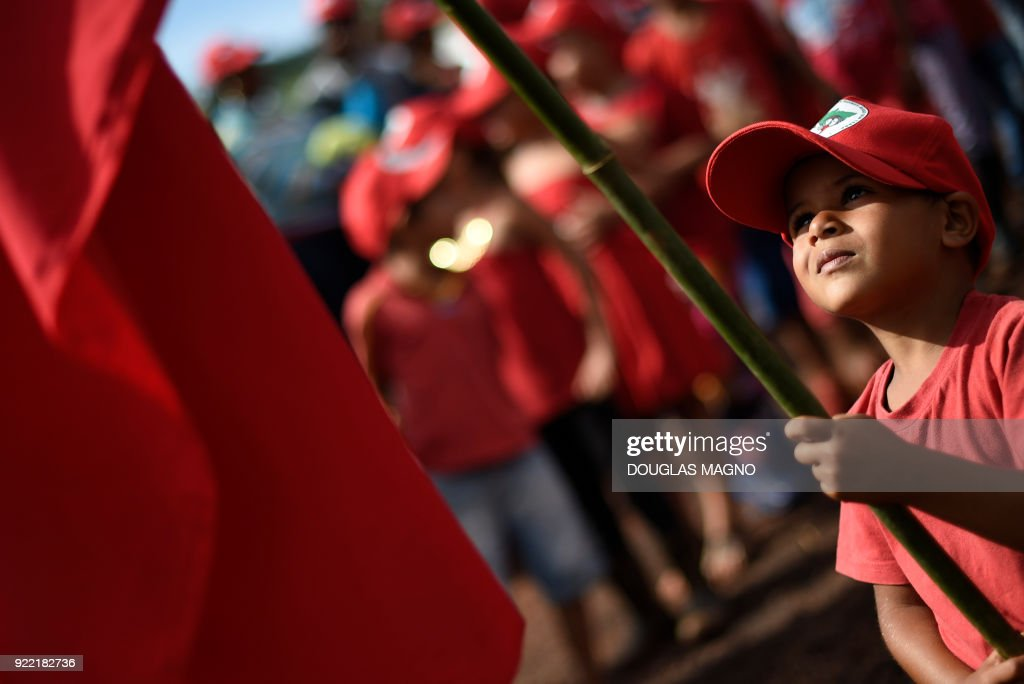 A boy holds a Landless Workers Movement flag during the visit of former Brazilian president Luiz Inacio Lula da Silva at their camp on the municipality of Itatiaiucu, metropolitan region of Belo Horizonte in the state of Minas Gerais on February 21, 2018. Brazil's former leftist president Luiz Inacio Lula da Silva made yet another appeal against a 12 year prison sentence for corruption that could knock him out of an attempted comeback election. /