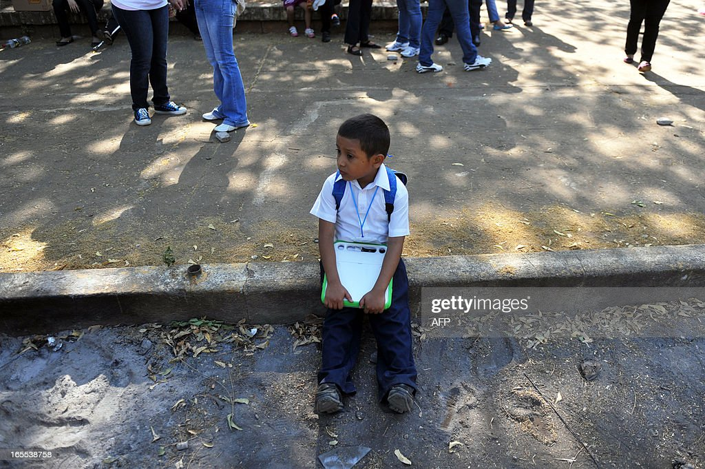 A boy holds a laptop as he receives one of the 3.000 XO notebooks donnated by the Zamora Teran Foundation, to support the campaign 'One Computer One Child', in Ciudad Sandino Managua's neighborhood on April 4, 2013. AFP PHOTO/Hector RETAMAL