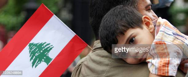 A boy holds a lebanese flag as he takes part in a march through central London 22 July 2006 protesting against Israeli attacks in LebanonThe Israeli...