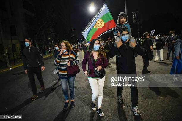 Boy holds a Mapuche indigenous flag as people celebrate while waiting for the official results of the referendum for a new constitution on October...
