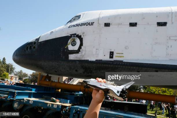 A boy holds a model of the Space Shuttle Endeavour as it is moved to the California Science Center on October 13 2012 in Inglewood California The...