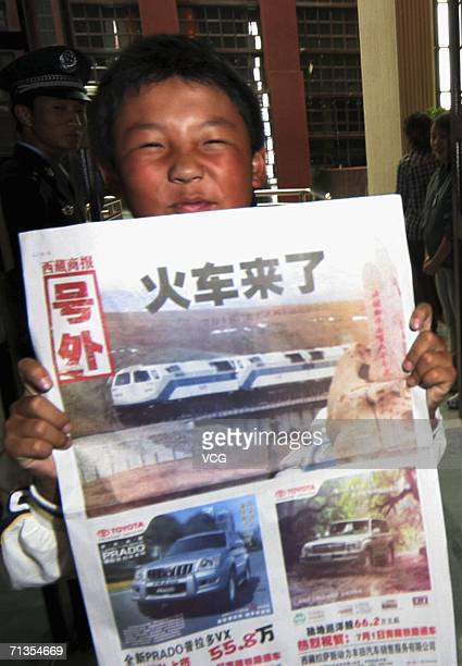 A boy holds a newspapaer reading 'Train is Coming' while waiting for the first train from Golmud Qinghai province to Tibet on July 2 2006 in Lhasa...