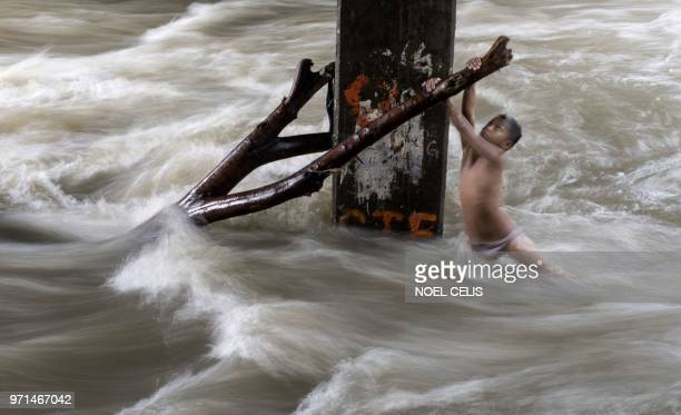 TOPSHOT A boy holds a partially submerged branch as he plays in a swollen river caused by heavy rains under a bridge in Manila on June 11 2018