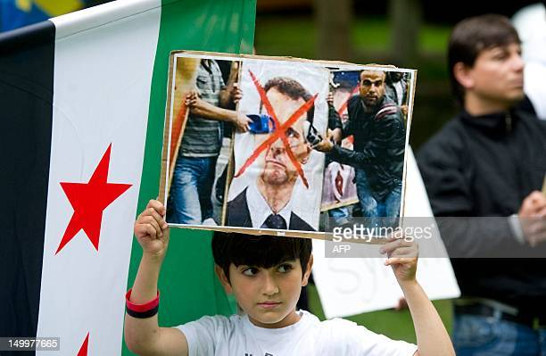 A boy holds a placard with a crossedover image of Syrian President Bashar alAssad on August 8 2012 outside the Russian embassy in Stockholm during a...
