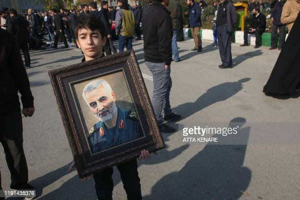 A boy holds a portrait of Iranian Revolutionary Guards Major General Qasem Soleimani during a demonstration in Tehran on January 3 2020 against the...