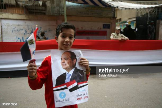 A boy holds a poster of Egyptian President Abdel Fattah alSisi on the last day of the 3day presidential elections on March 28 2018 in Cairo Egypt...