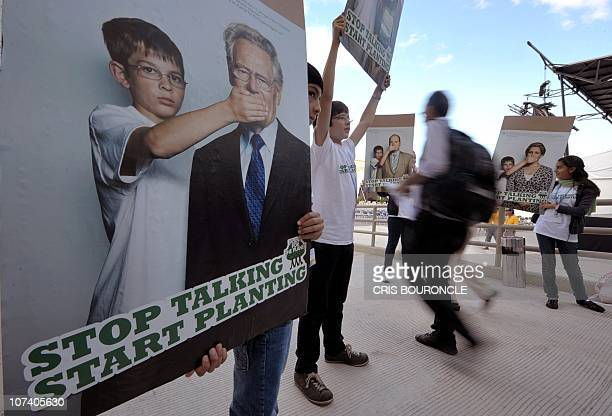 A boy holds a poster with an image of Swiss theologian Hans Kung in a throughway of the Cancun Meese Convention Center on December 8 with the motto...