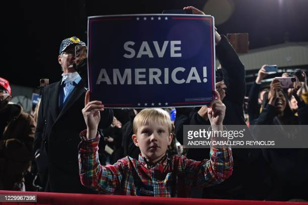 "Boy holds a ""Save America"" sign as US president Donald Trump speaks at a rally to support Republican Senate candidates at Valdosta Regional Airport..."