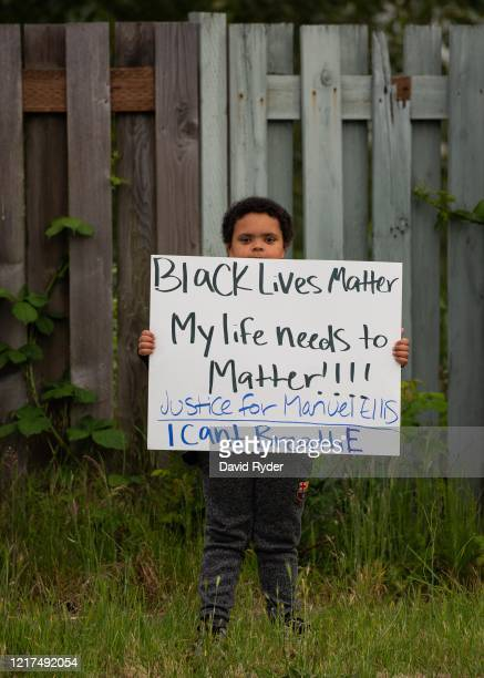 A boy holds a sign during a vigil for Manuel Ellis a black man whose March death while in Tacoma Police custody was recently found to be a homicide...