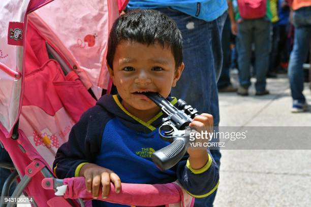 A boy holds a toy gun while his parents take part in the Migrant Via Crucis caravan towards the United States and participate in a protest against...