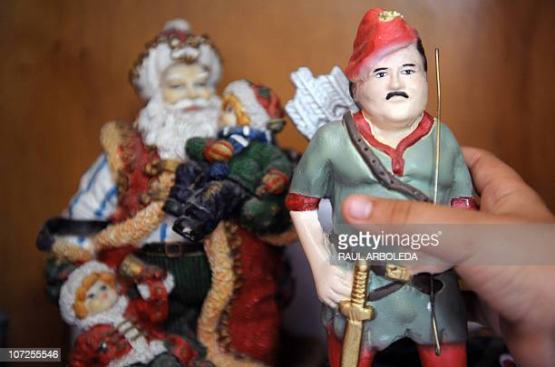 A boy holds a toy respresenting Colombian drug lord Pablo Escobar dressed up as Robin Hood inside his house at Pablo Escobar neighborhood on December...