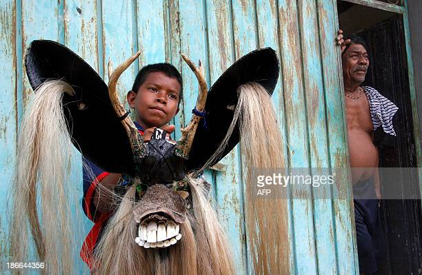 A boy holds a tradinonal mask of the AfroMexican Dance of the Devils in Cuajinicuilapa community Guerrero state Mexico on November 2 2013 The Dance...