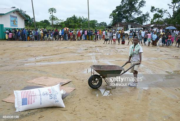A boy holds a wheelbarrow next to a bag of rice on the ground as others wait during a food distribution by the World Food Programme in Dolo's Town...