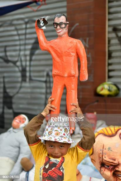 A boy holds an effigy representing Ecuadorean suspended VicePresident Jorge Glas as masks and effigies of politicians artists or social figures or...