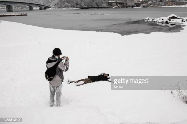 A boy holds an electronic device to film a boy lying in the snow