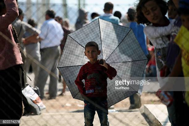 A boy holds an umbrella Refugee camp in Skaramaga area a port town 11 km west of Athens A large camp is being constructed here with a big capacity...