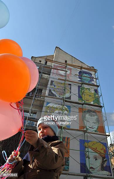 A boy holds balloons as he takes a part in ceremony of the opening of a mosaic panel made on a gable end of an apartment house in central Kiev on...