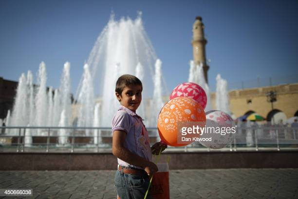 Boy holds Happy Birthday balloons outside the Qaysari Market on June 15, 2014 in Erbil, Iraq. In Iraq's capital city of Baghdad and other towns and...