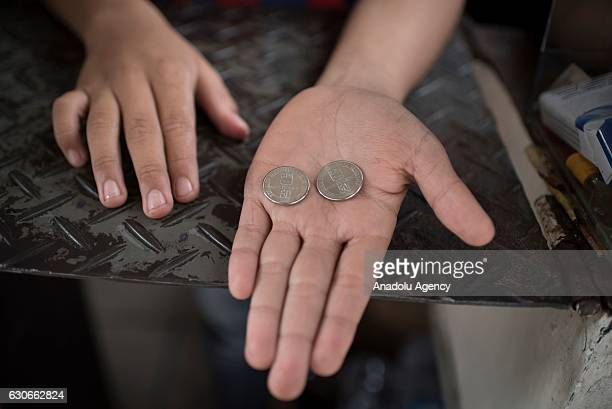 Boy holds new 50-Bolivar-coins in downtown Caracas on December 29, 2016. Venezuela took delivery on December 27 of its third load of new, bigger...