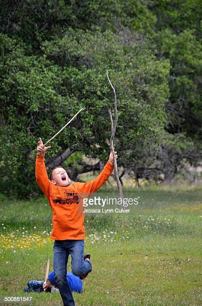 a boy holds up sticks in a victory dance - lynn pleasant photos et images de collection