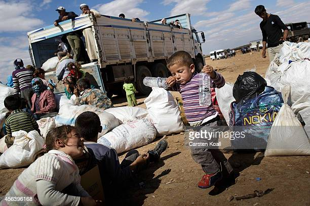 A boy holds water bottles after crossing the border from Syria into Turkey September 30 2014 near Suruc Turkey Kurdish troops are engaged in a battle...