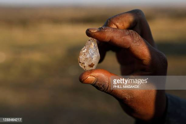 Boy holds what he believes to be a diamond after the discovery of unidentified stones at KwaHlathi village near Ladysmith, South Africa, on June 15,...