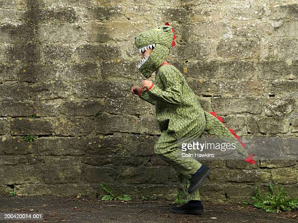 Boy (5-7) hopping by brick wall in crocodile costume, side view