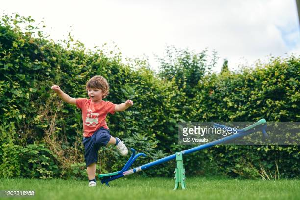 boy hopping off toy seesaw in garden - play off stock pictures, royalty-free photos & images