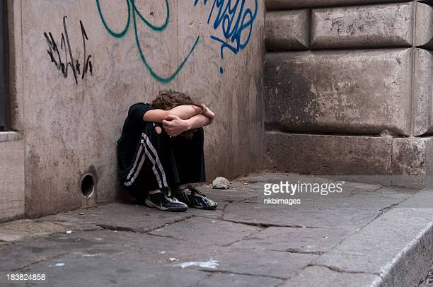 boy huddled and alone on city street - black alley stock photos and pictures