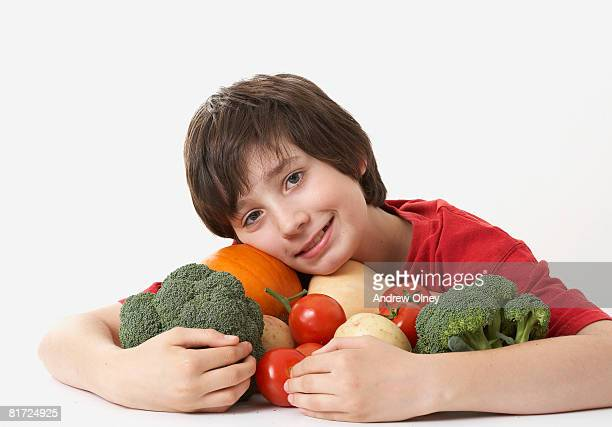 Boy hugging a pile of assorted vegetables smiling