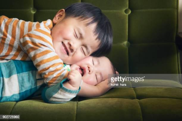 ソファーで抱き締める男の子 - 兄弟 ストックフォトと画像