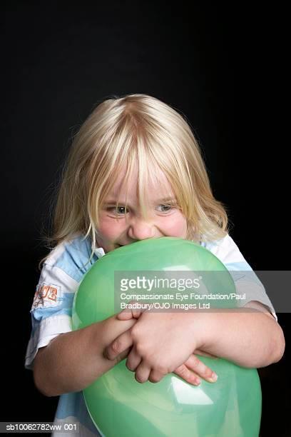 Boy (4-5) hugging balloon