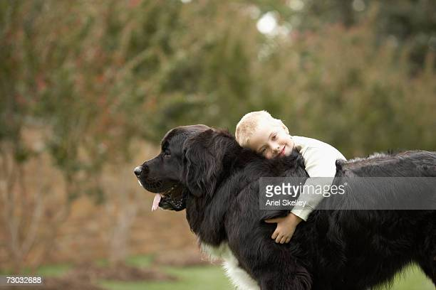 Boy (6-7) hugging black Newfoundland outdoors