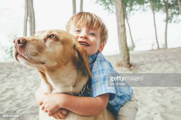 Boy hugging dog on wooded beach