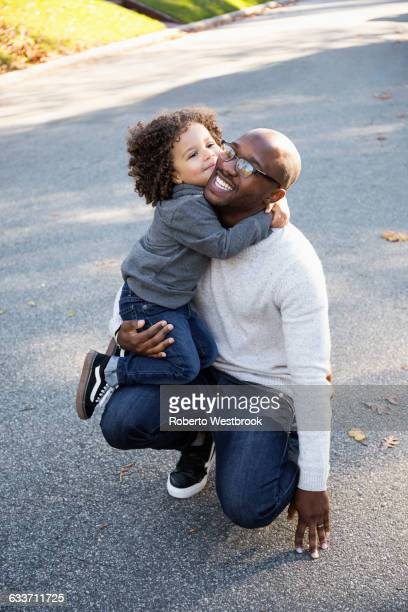 Boy hugging father outdoors