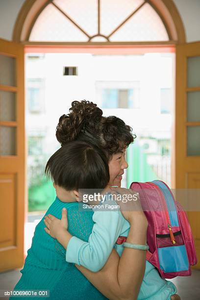 Boy (4-5) hugging grandmother before leaving school, side view